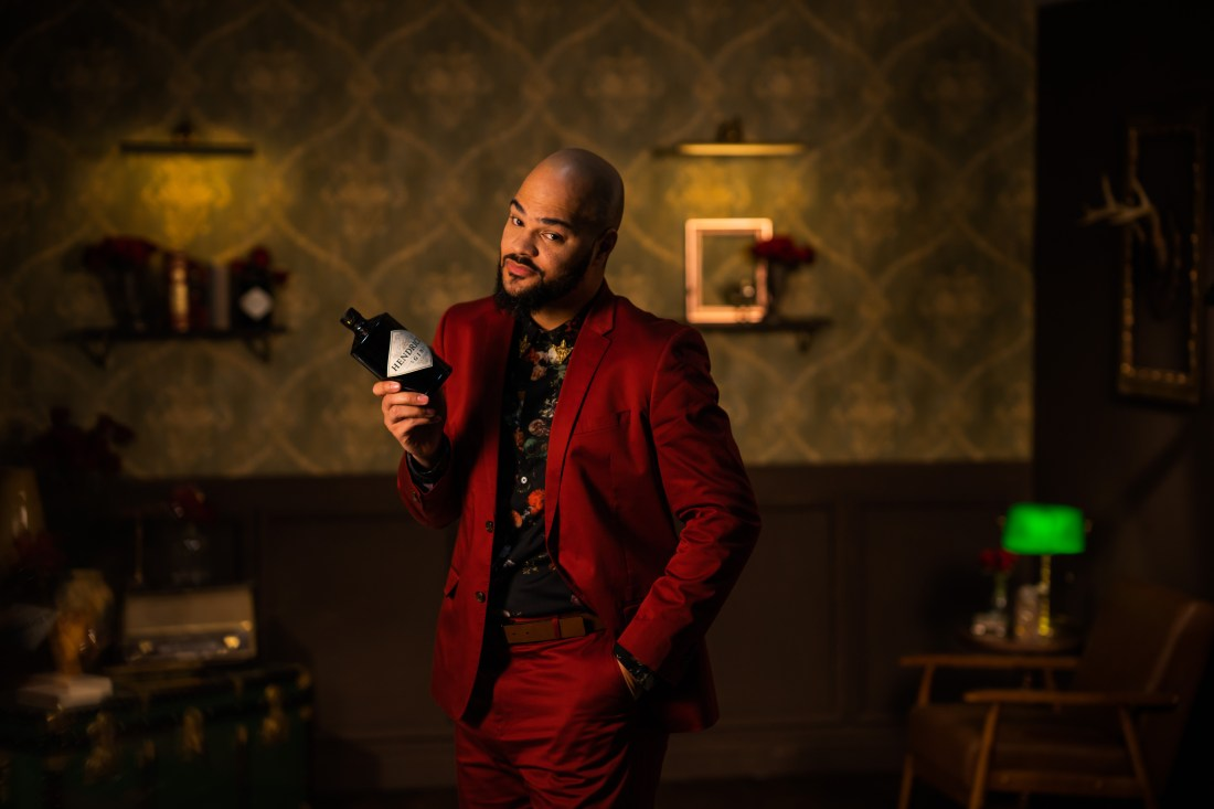 dashing man in a red suit, holding a gin bottle in a swanky bar scene