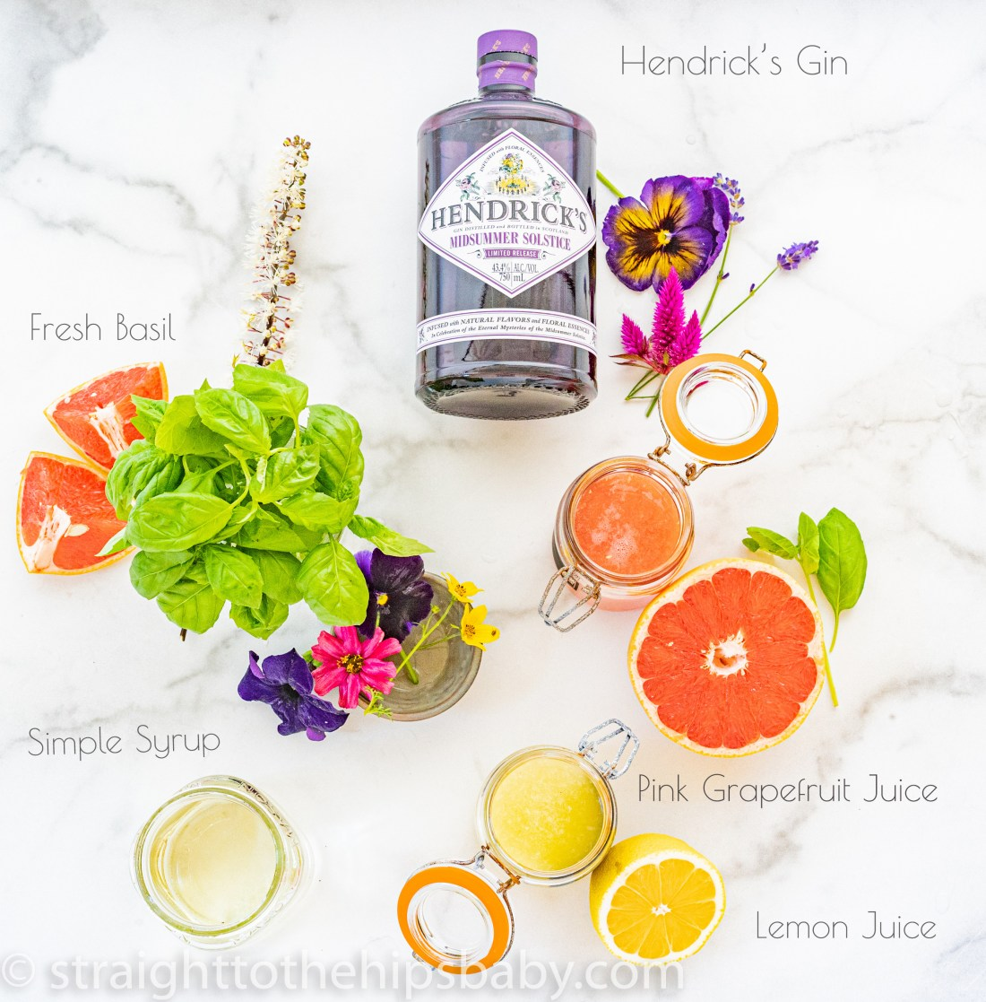 ingredient flat lay; lemons, grapefruits, basil, flowers, and simple syrup in jars. A purple bottle of gin lays flat at the top of the photo