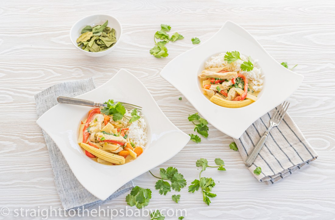 two finished plates of turkey green curry on a light colored background, with scattered cilantro