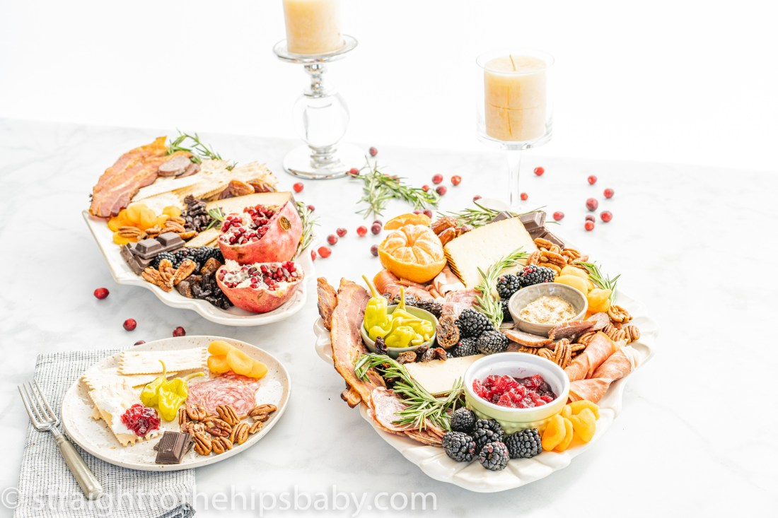 two laden charcuterie platters with brightly colored fruits, cheeses, and meats