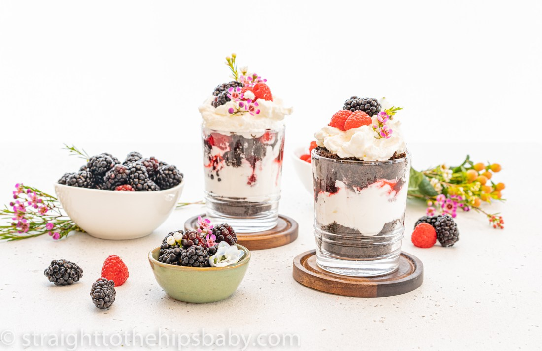 two finished chocolate raspberry trifles with champagne cream on a white background with bowls of fresh berries and flowers