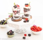 two chocolate trifles on a white cake stand with bowls of berries and flowers