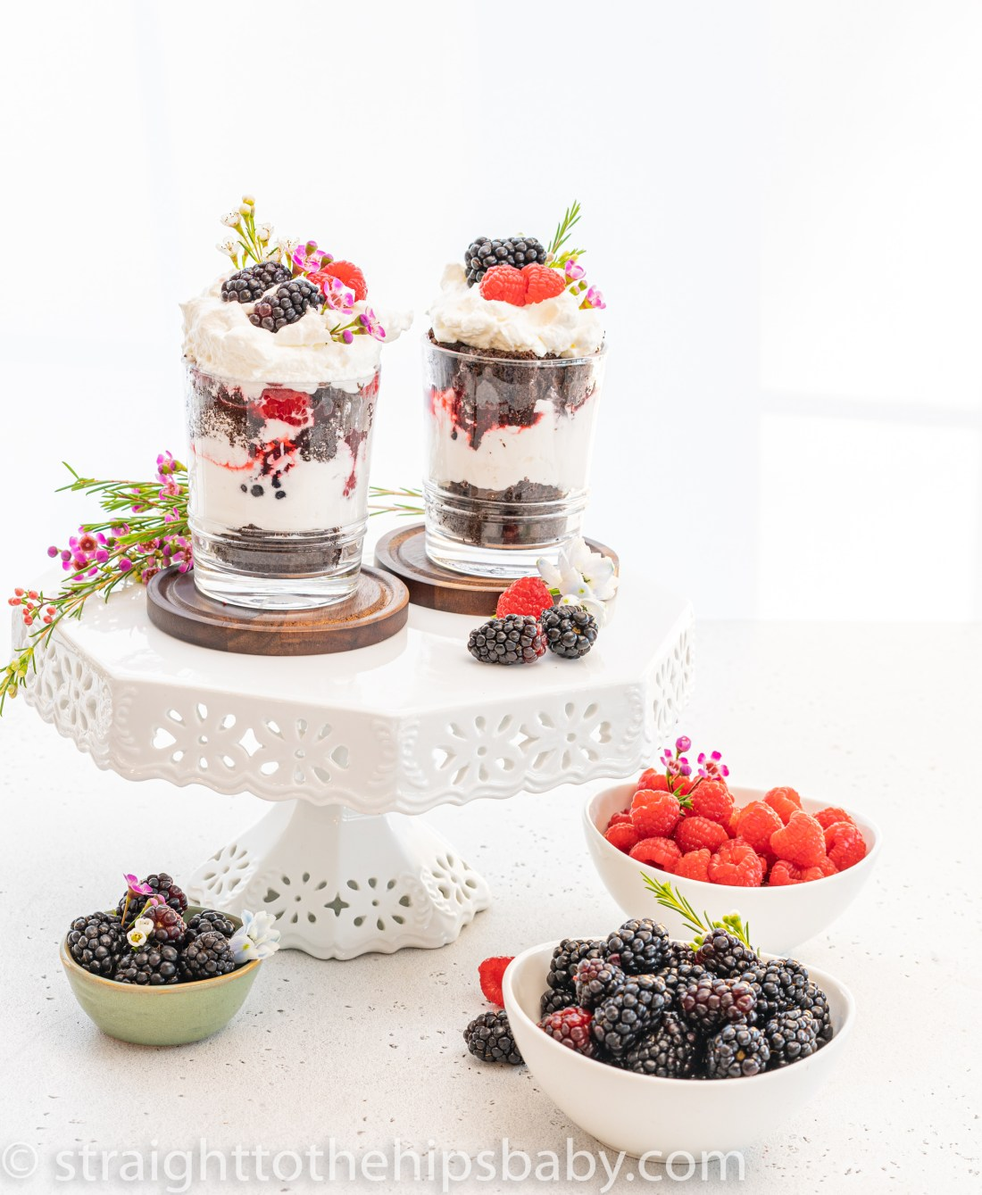 two chocolate raspberry trifles on white cake stand with flowers and bowls of berries