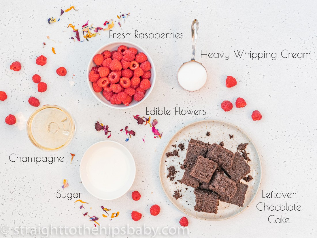 ingredient flat lay including a plate of chocolate cake, bowl of raspberries. fresh cream, a coupe glass of champagne, and a copper measuring cup of sugar