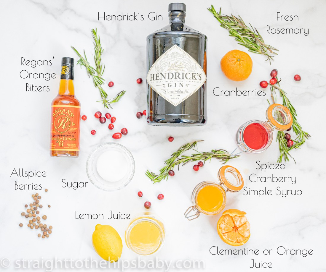 cocktail ingredient flat lay with gin, clementine, cranberries, rosemary, and allspice