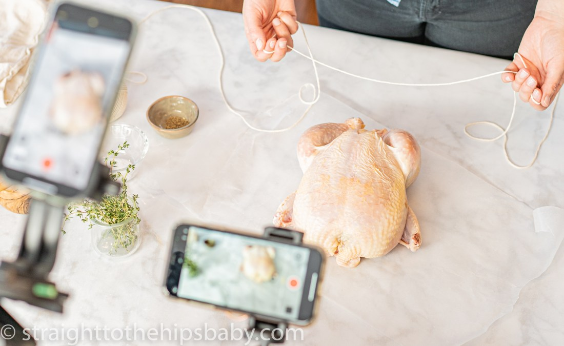 trussing a chicken with butcher's twine, while video taping with two iPhones