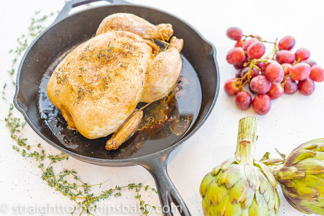 a roasted chicken in a castiron pan, surrounded by raw artichokes and grapes