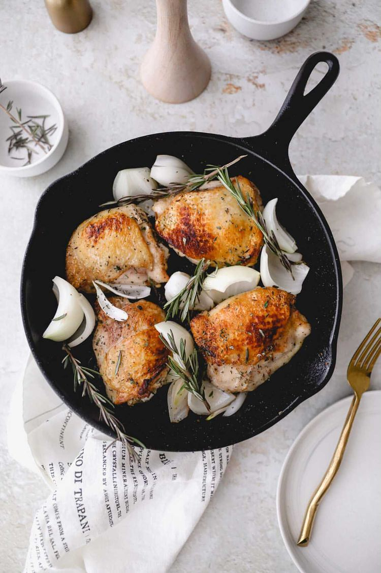 a cast iron skillet with perfectly golden roasted chicken pieces