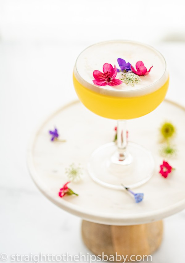 a finished lemon flora gin sour, on a white background, garnished with fresh flowers