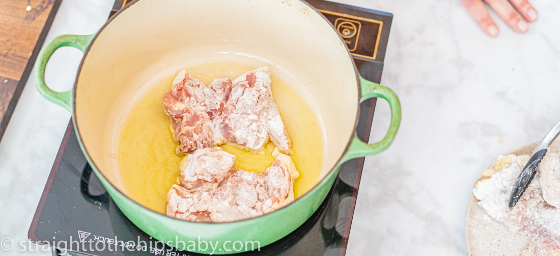 a green dutch oven, frying chicken thighs,mon a marble background