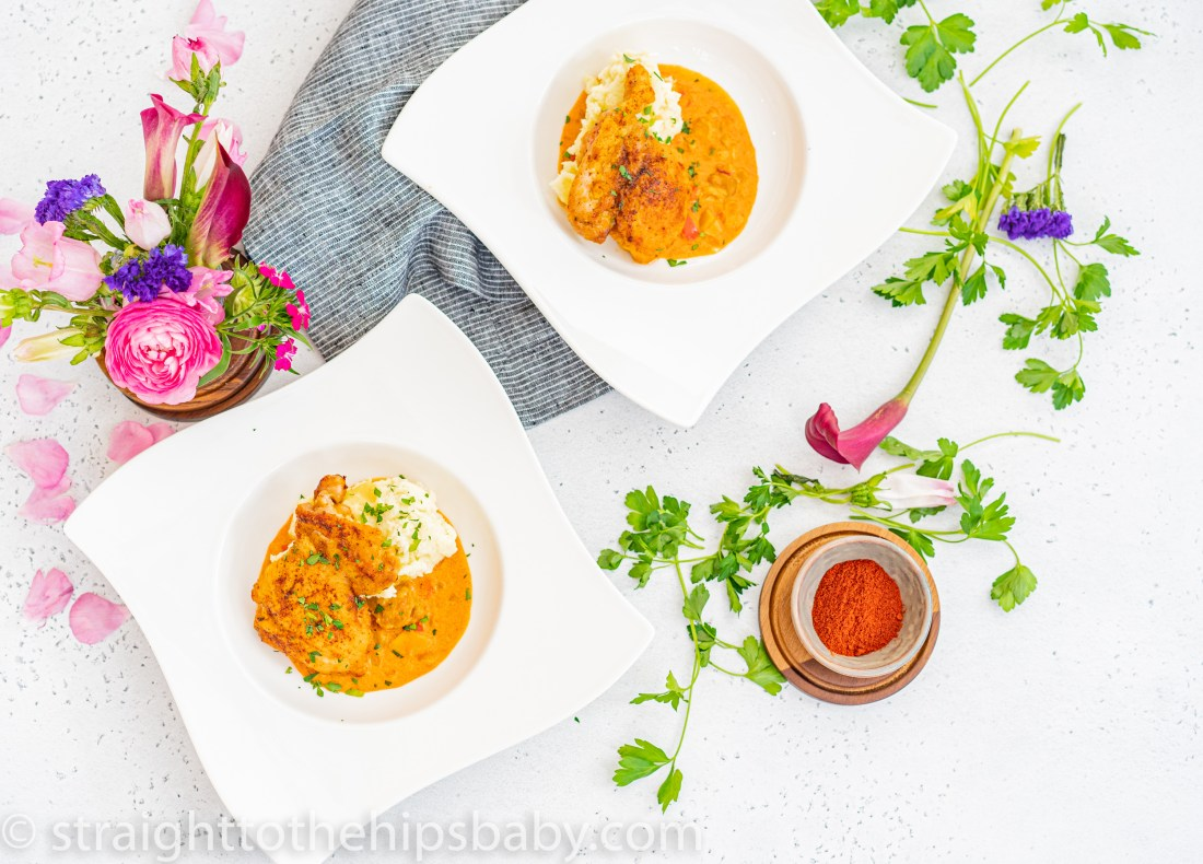 2 white square bowls, overhead view, with a small bowl of ground smoked paprika and flowers surrounding the bowls