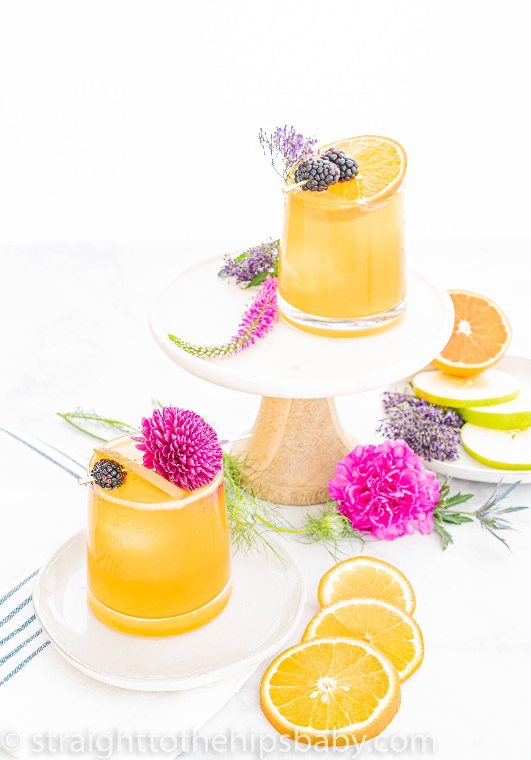 two finished apple & orange bourbon sours surrounded by flowers on a white background