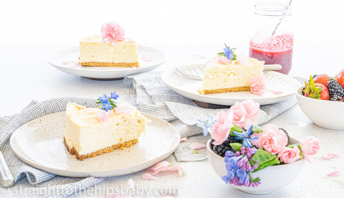 3 pieces of sesame cheesecake on earthenware dishes, surrounded by pastel colored spring flowers