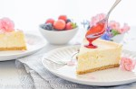 two slices of creamy white cheesecake, on a white background with pick flowers, spooning on a rich red plum sauce
