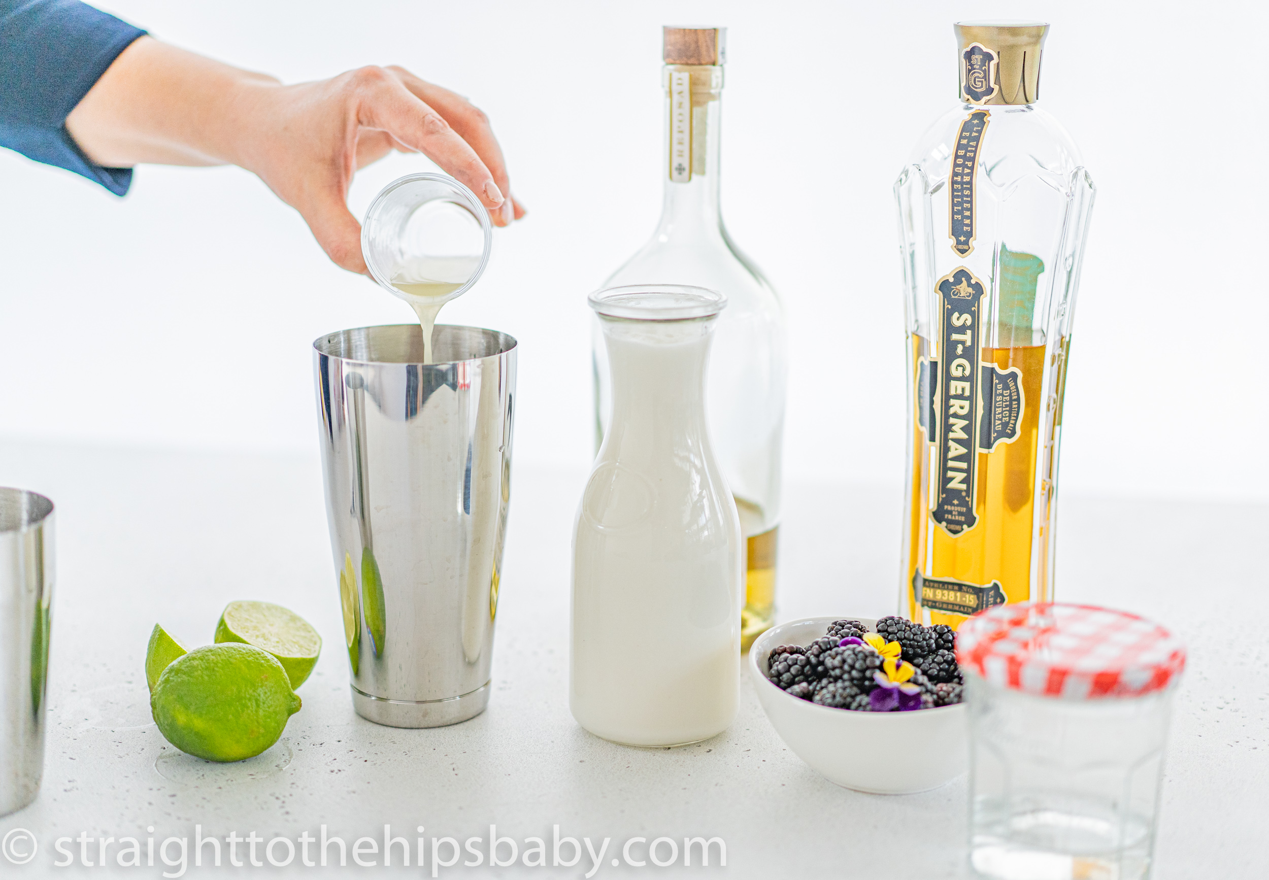 pouring coconut milk into a cocktail shaker, with bottles of St Germain and tequila in the background