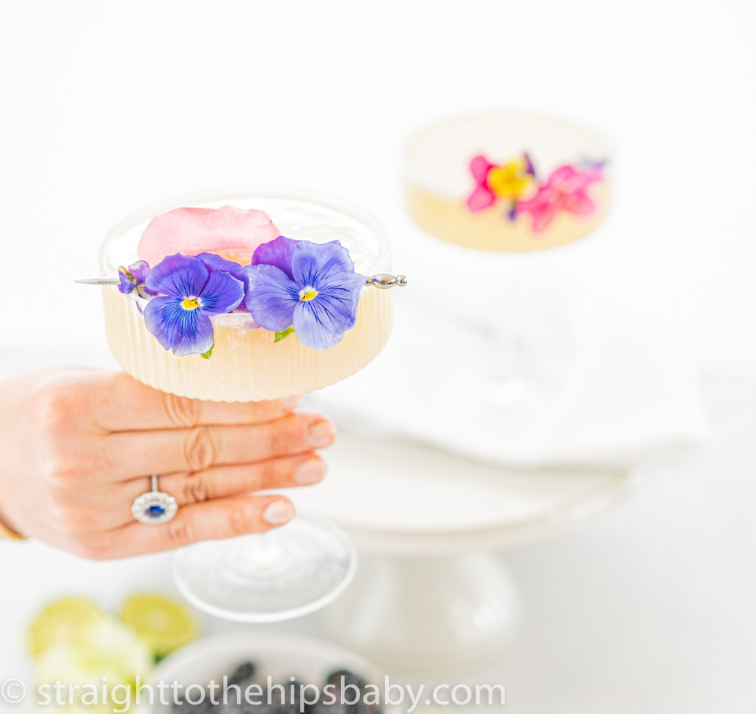 a woman's hand holding a creamy coconut Paloma garnished with pansies