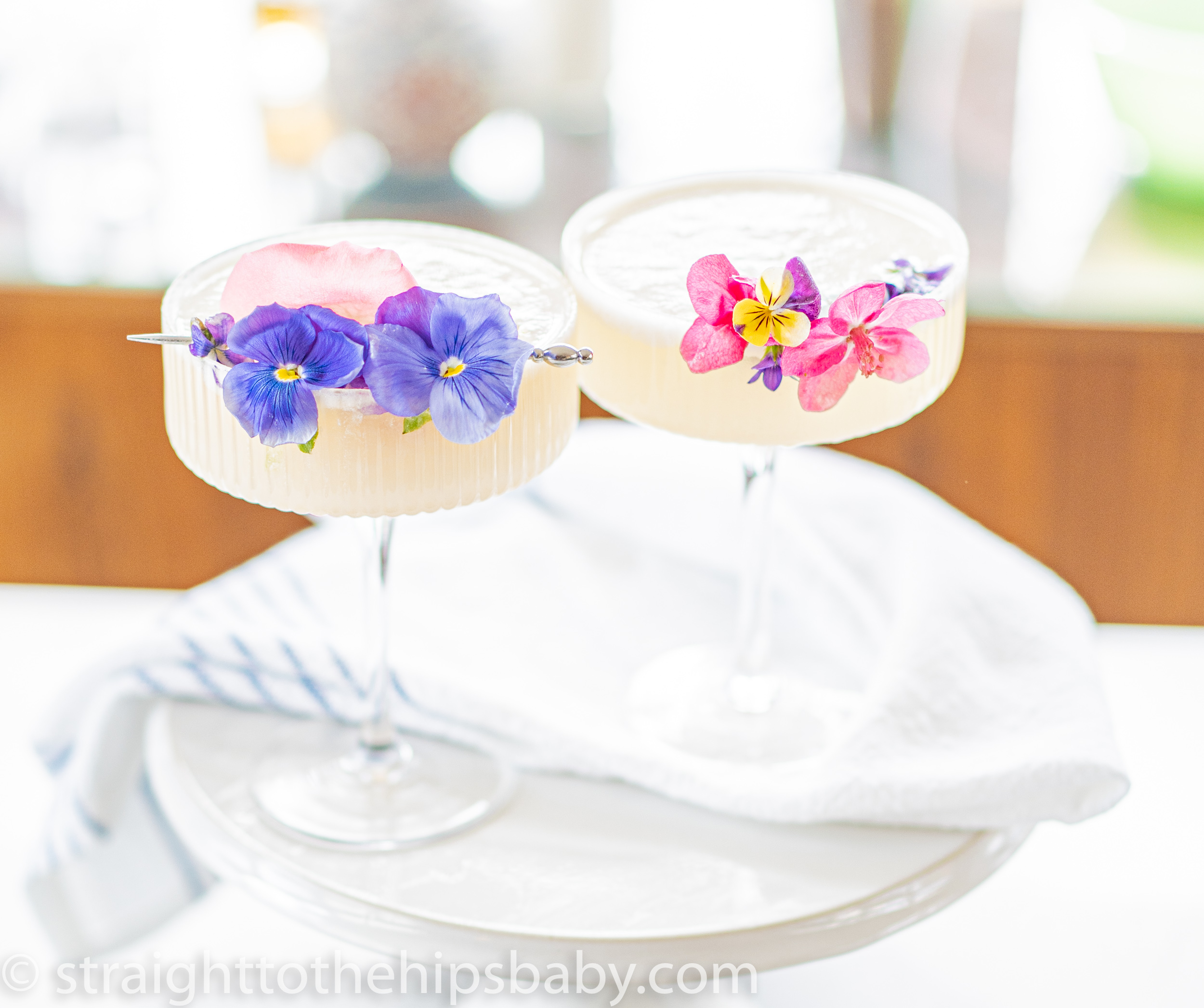 two coupe glasses filled with a coconut lime Paloma cocktail