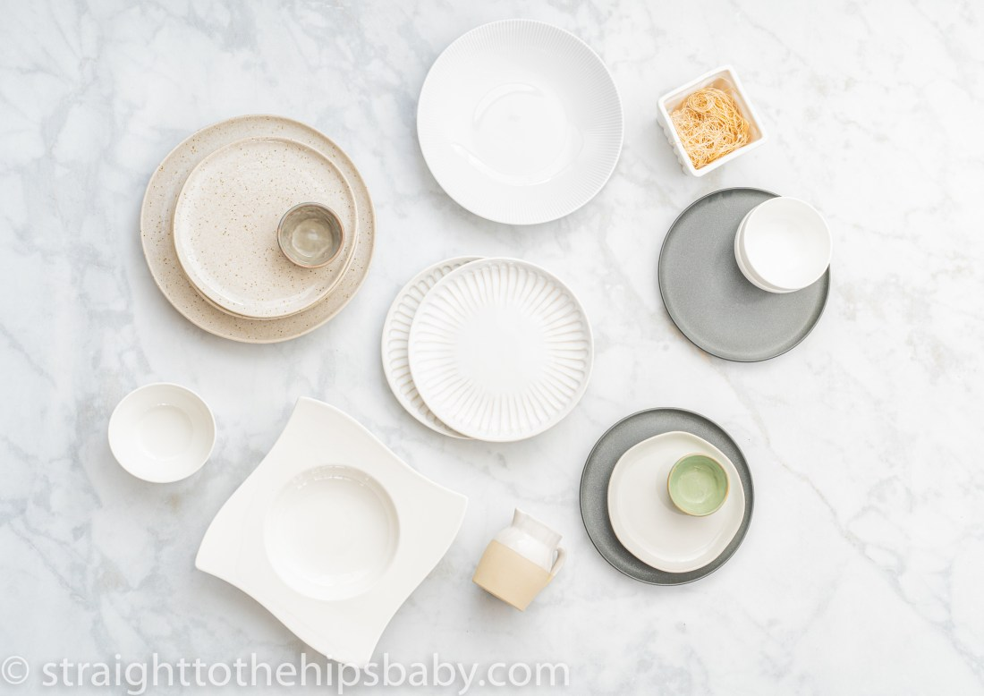 a series of different colored plates and china for food blogging and food styling. Food photography prop essentials