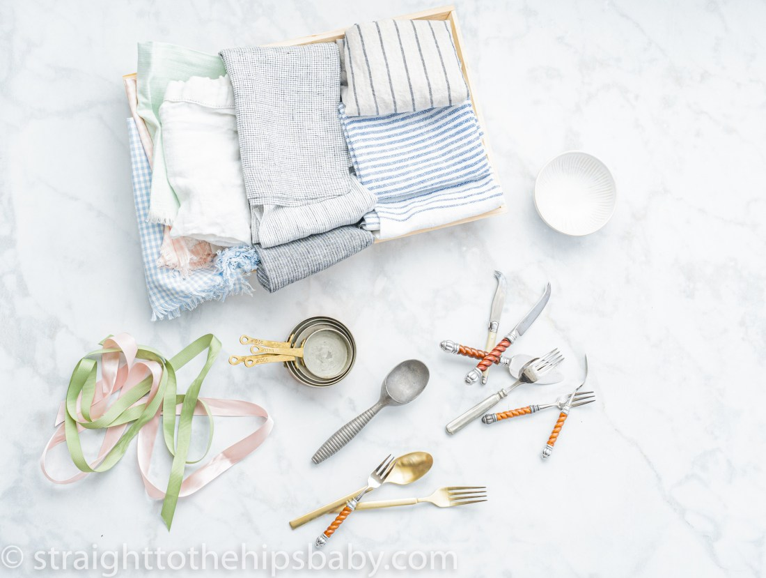 food props are important to your for photography. neutral colored linens, utensils, and measuring cups at a sense of place. Here, a basket of natural colored linens and a scattering of vintage silverware on a light colored background, help set the scene