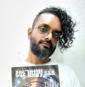 An amazingly talented person, with their head tilted to the side, looks at the camera. They have dark, curly hair, with shaved sides. They're holding an issue of Translations Magazine.