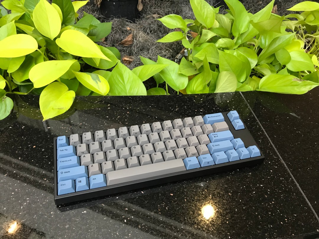 An FC600M keyboard sitting in front of a fake plane, with grey and blue keycaps.