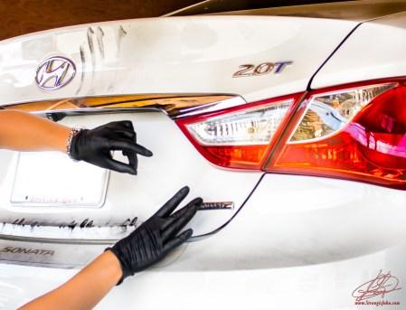 Crime scene technician gathers prints from the trunk of the stolen Hyundai Sonata.