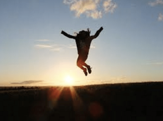 A woman jumping because she's feeling motivated, the opposite of feeling unmotivated
