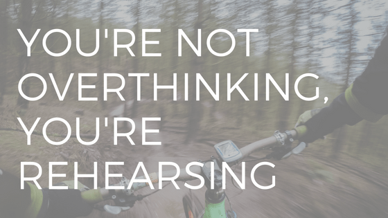 "text ""youre not overthinking you're rehearsing"" over a racer on a mountain bike"