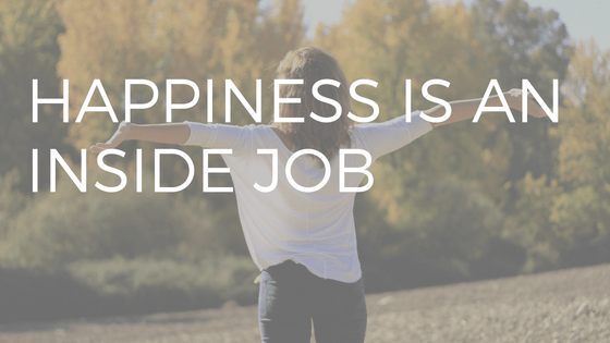 "TEXT ""HAPPINESS IS AN INSIDE JOB"" OVER PHOTO OF WOMAN WITH WHITE TOP AND BROWN HAIR JUMPING FOR JOY IN FRONT OF A FALL TREES BACKGROUND"
