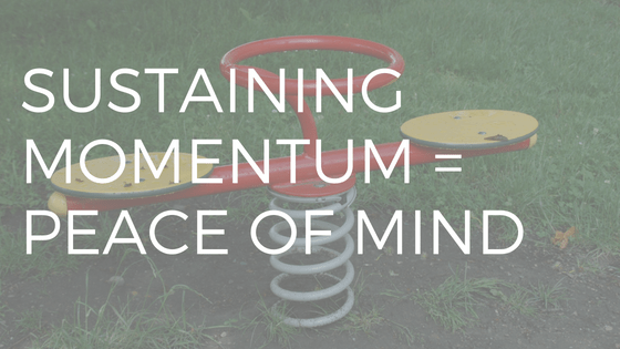 SUSTAINING MOMENTUM = PEACE OF MIND (WHITE TEXT OVER PICTURE OF RED METAL CHILDREN'S SEE SAW IN PLAYGROUND)