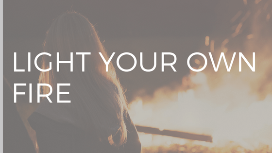"WHITE TEXT READING ""LIGHT YOUR OWN FIRE"" OVER PHOTO OF WOMAN WITH LONG BLONDE HAIR LOOKING AT A BLAZING BONFIRE"