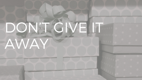 "STack of presents wrapped in grey wrapping paper with white text over top reading ""don't give it away"""