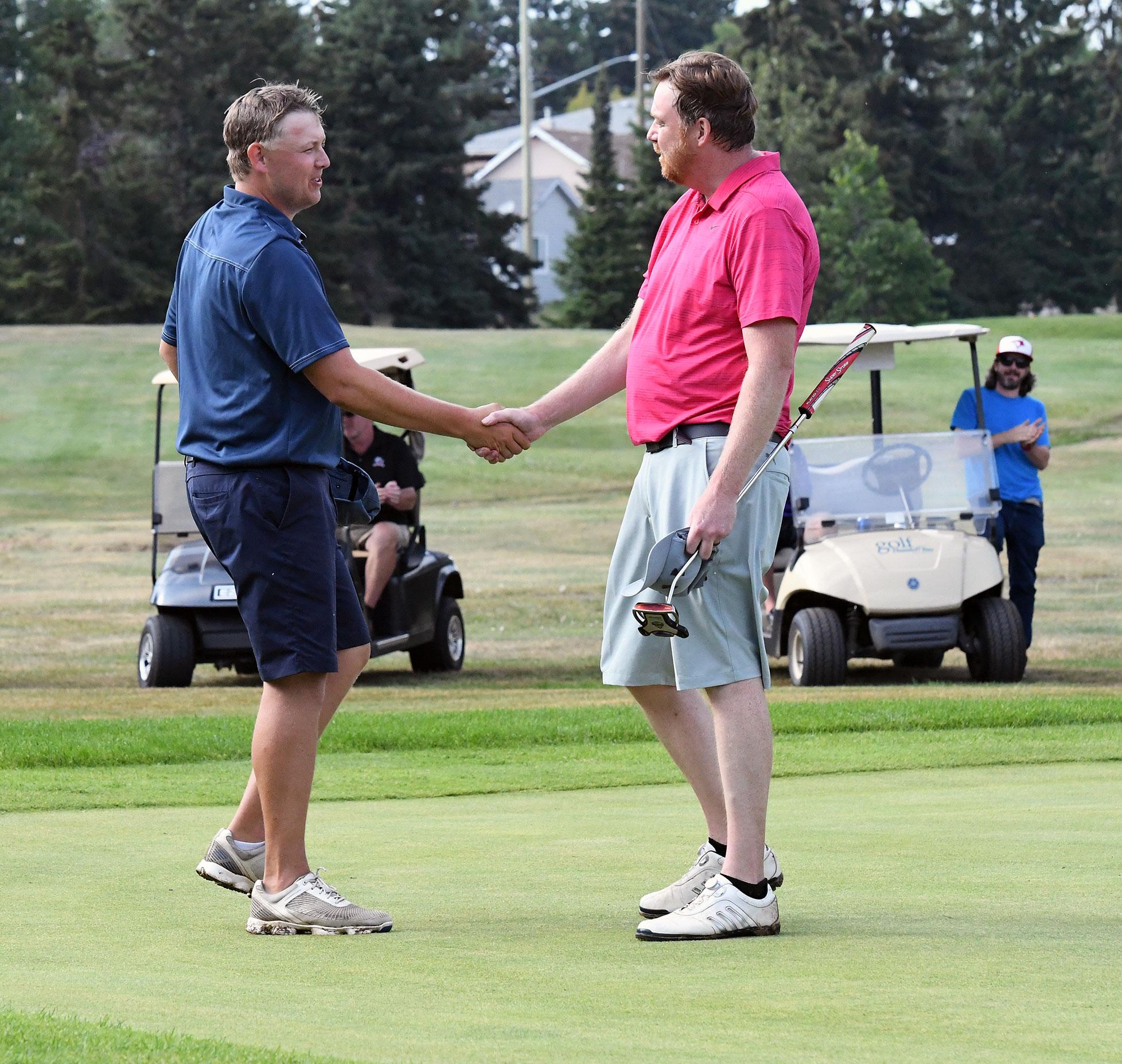 Scott Wilke and Robert Cumming shaking hands.