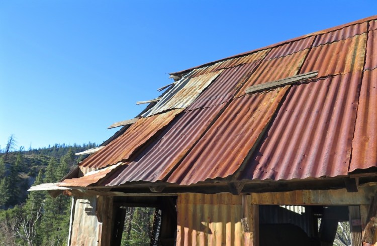 The small two story cabin is roofed and sided with corrugated tin shingles and is still standing after all these years.