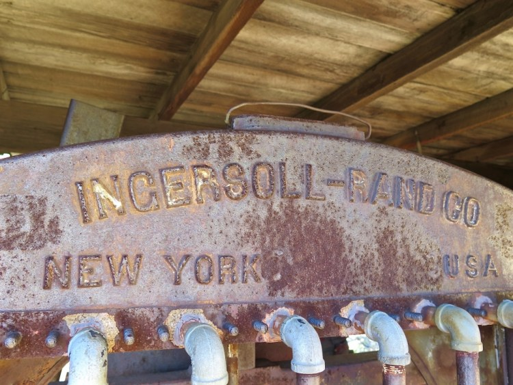 "There's also a fairly preserved 8 cylinder compressor on metal wheels. It is marked ""Ingersoil-Rand Co"" with the numbers '1942' and contains an iron boiler with lettering stating it was tested on 11/03/23."