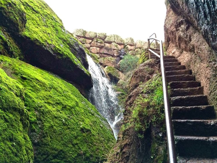 The ascent up from the talus caves includes a view of a mossy waterfall and the reservoir dam wall.
