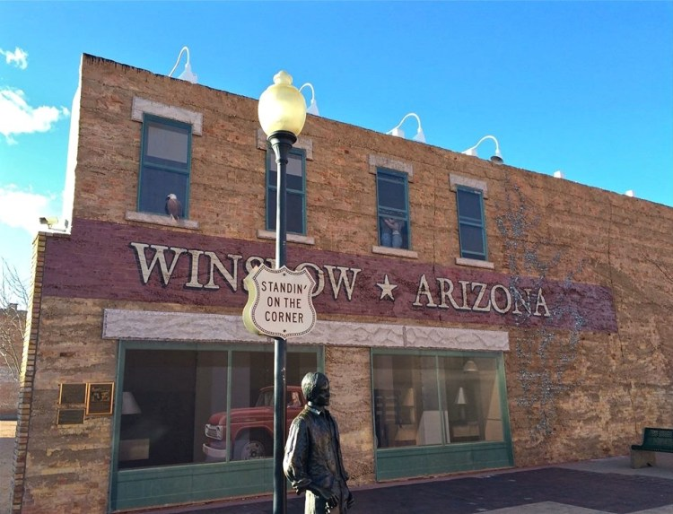 "Is a passing mention in a 40+ year old rock song lyric cause for civic celebration? In Winslow it sure is. When the Eagles first decided to ""Take it Easy"" in a song written by Jackson Browne and Glenn Frey, the reference to ""standing on a corner in Winslow Arizona"" was just a catchy almost-rhyme. But the song has endured on classic rock radio, a sleepytime anthem for aimless 1970s wandering. In 1999, the town of Winslow put the finishing touches on their ""Standin' on the Corner"" Park. The downtown corner was designed to include a life-size statue of a relaxed dude-with-guitar and a two-story Trompe L'oeil mural laying out all the critical lyrics: ""a girl"" and ""a flatbed Ford"" reflected in a storefront, along with an eagle perched on one painted window sill."
