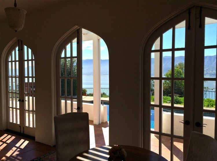 The great room has large arched French doors that run along both sides providing views of the courtyard at the front of the house and the pool and lake in the back.