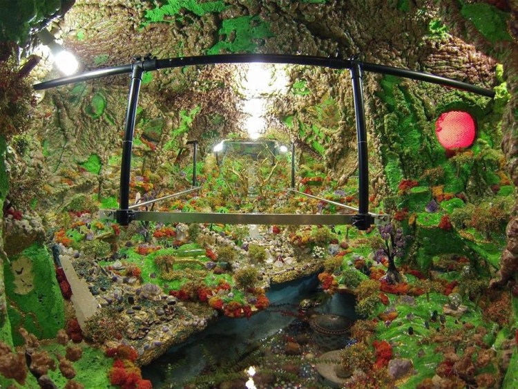 Most people peer through the portals to view the flowing river, gems, fake moss and undulating levels of spray insulation covered in bright paint.