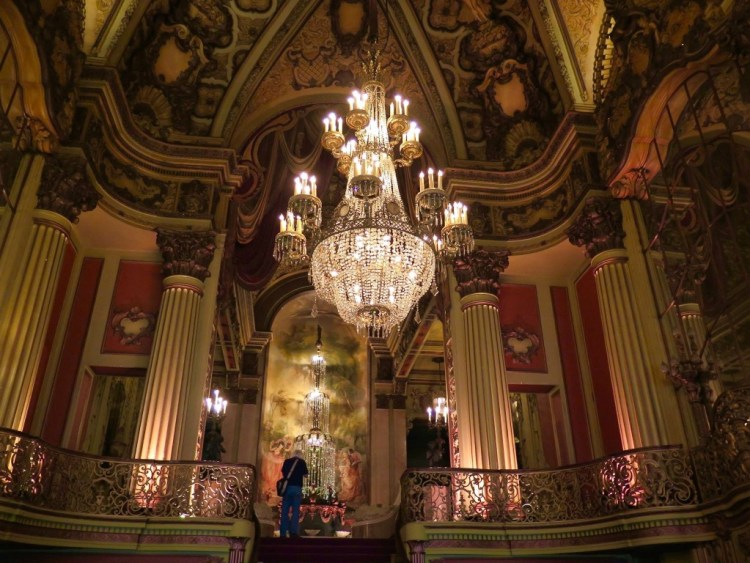 The opulent fifty-foot-tall lobby, complete with crystal chandeliers and a grand staircase leading up to the mezzanine level.