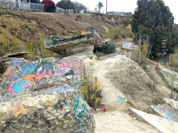 A torn up graffiti covered road is a constant reminder of what could happen to the neighborhood that sits above it.