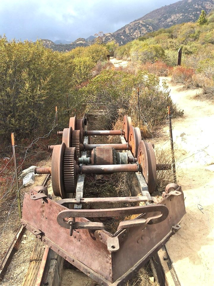 One 750 pound motorized drive wheel and two 500 pound dummy trucks with a snow plow mounted on rails over the service pit. Recovered in 1993 from the downhill side of Echo Mountain.