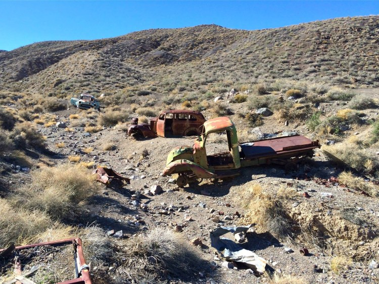Rusted out vehicles from the 30's and 40's litter than canyon leading up from the ruins.