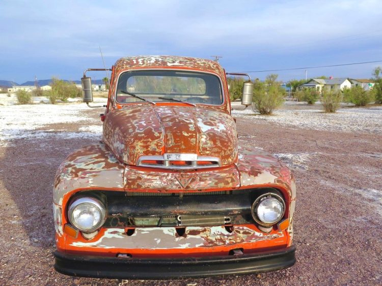 A 1951 Ford pickup with a lovely rusted patina sits out in front.