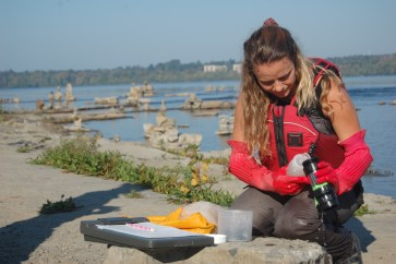 Living Lakes Canada representative Raegan examines benthic invertebrate sample at Remic Rapids (c) Rebecca Spring WWF