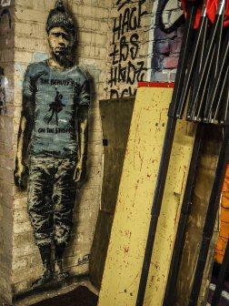 in der Ecke einer Halle steht hinter ein paar Brettern ein Junge, von LET gemalt