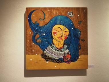The Art of Pau zeigt eine Frau mit blauen Haaren auf einem Holzhintergrund