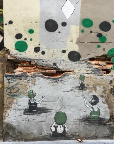 junge Frauen mit Badekappen stehen im Wasser und scheinen mit Wasserbällen in grün und schwarz zu spielen