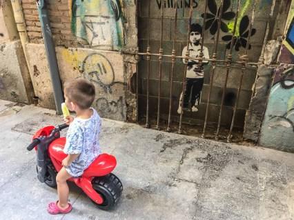 das Foto zeigt einen Jungen mit einem Eis auf einem roten Plastikfahrzeug vor einem Stencil von Tona, das einen Jungen hinter einem Türgitter zeigt