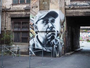 die Künstler El Mac und Kofie haben in einem Hinterhof eine Hausecke mit einem Portrait gestaltet
